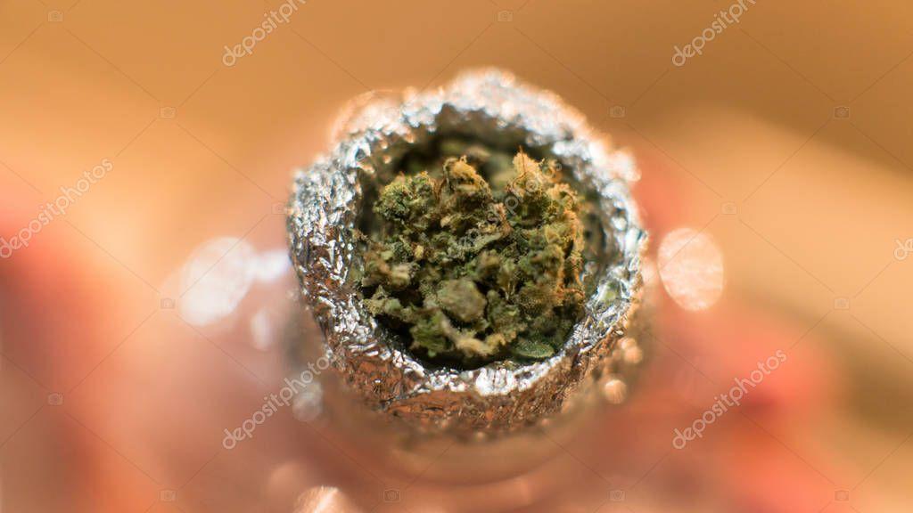 Smoking marijuana through a plastic bottle macro view