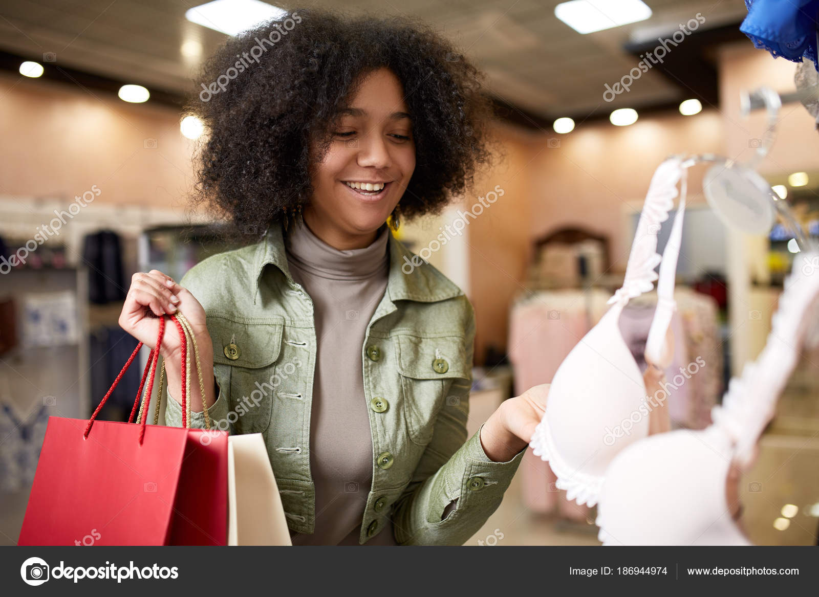 7c8a988bf Young attractive african american woman choosing pretty bra in lingerie  store. Black mixed race girl choosing underwear in shop and holding paper  shopping ...
