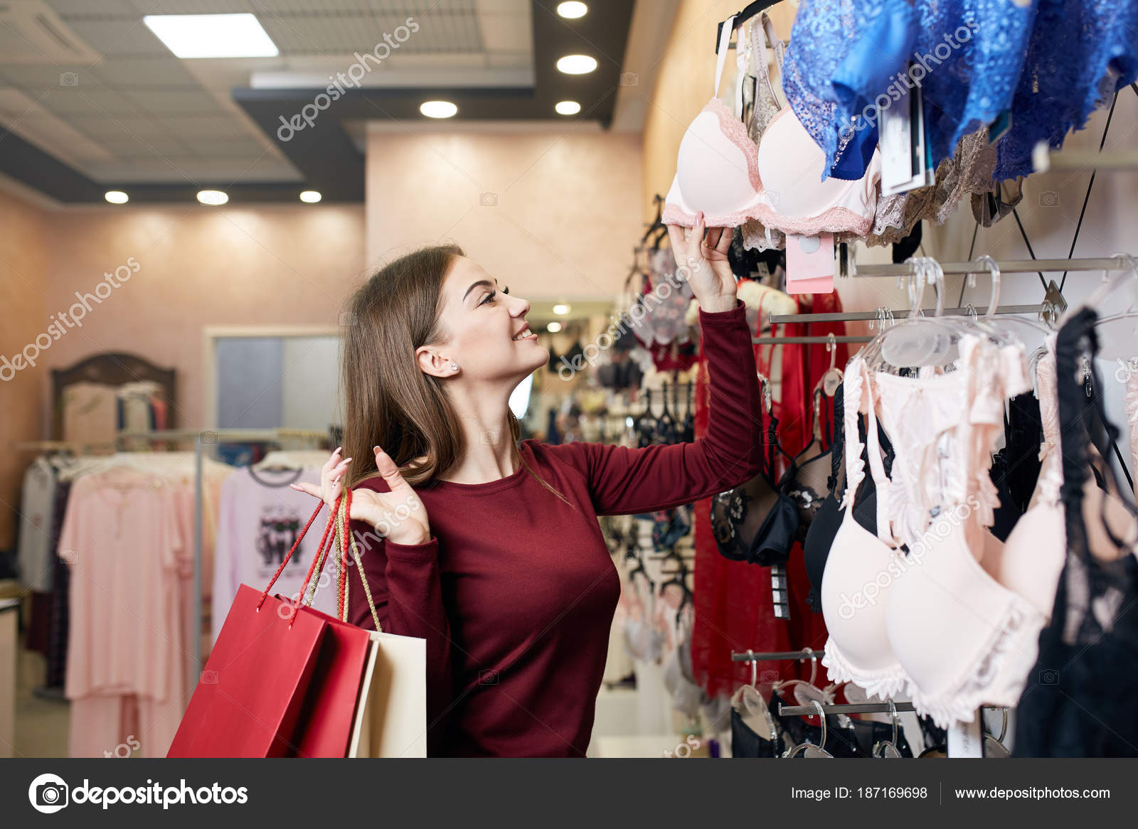 5ae53cd577e12 Young woman chooses sexy brassiere among set in a boutique. Pretty girl  considers bra with shopping bags in her hand in underwear store.
