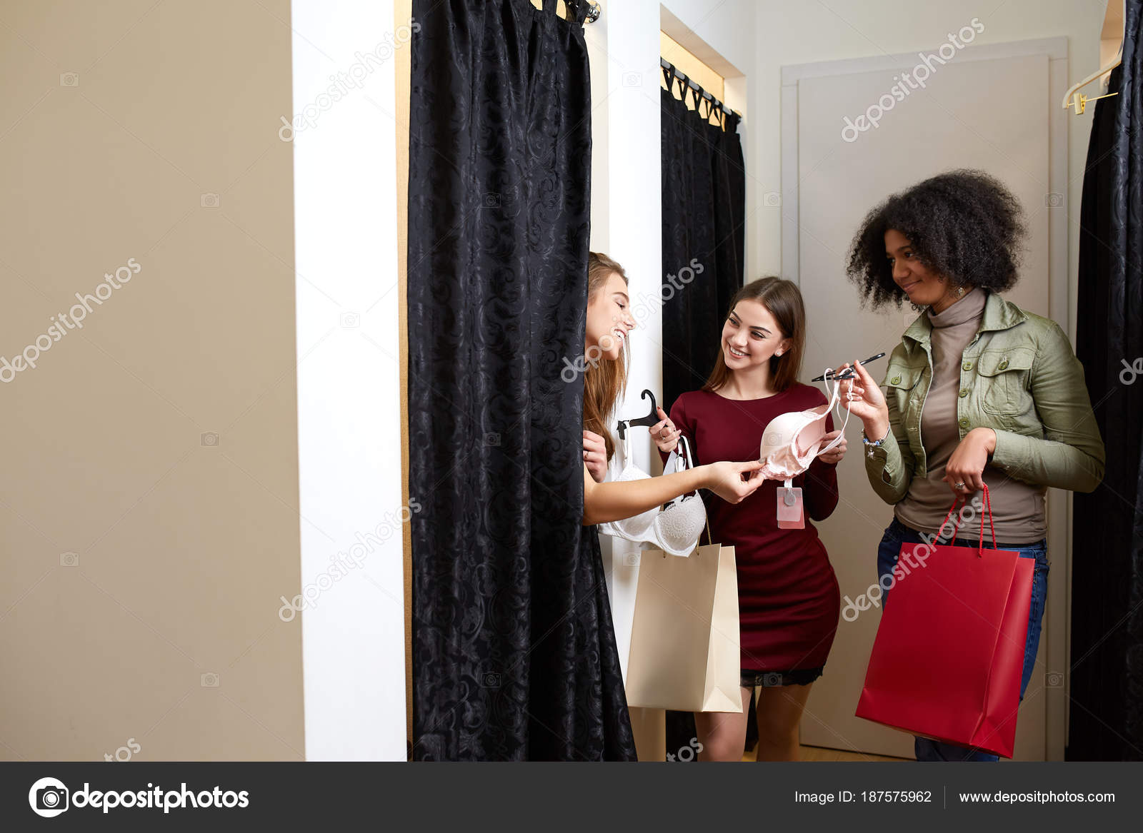 c01848103 Beautiful young woman asking for a friends opinion in the fitting room of lingerie  store. Female tries on bra in underwear shop. Shop assistant helps girl ...