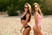Két suntanned meg, a strandon napozással és a szórakozás. Cserzett irls és stílusos fürdőruha és napszemüveget visel a nap. Pózol a tenger partján, a nyári szép nők