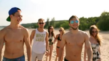 Group of friends walking on sunny beach. Young tanned cheerful caucasian people walking, chatting and laughing by sea on summer. Men and women wearing swimwear and bikini. Lifestyle slow motion video.