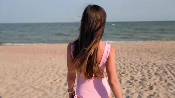 Hátulnézet nő séta tengerparton kövesse őt a nyaralás utazás tengervíz, fordul és kéri. Lady, slim forró tested, trópusi fehér homokos strand visel rózsaszín fürdőruha megy az óceán