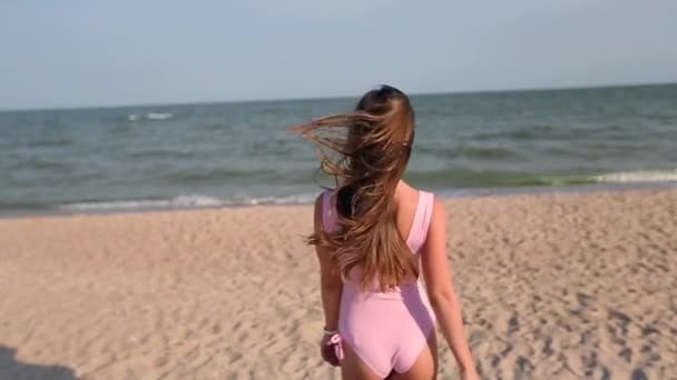 Back view of woman walking on beach to the sea water, turns and invites to follow her on vacation travel. Lady with slim hot body on tropical white sand beach wearing pink swimsuit goes to the ocean.