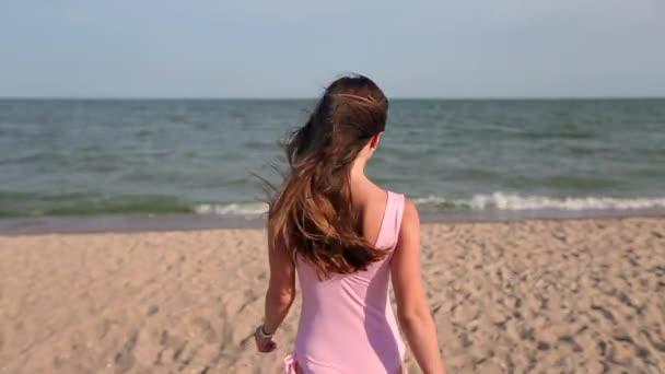 Hátulnézet nő séta tengerparton kövesse őt a nyaralás utazás tengervíz, fordul és kéri. Lady, slim forró tested, trópusi fehér homokos strand visel rózsaszín fürdőruha megy az óceán.