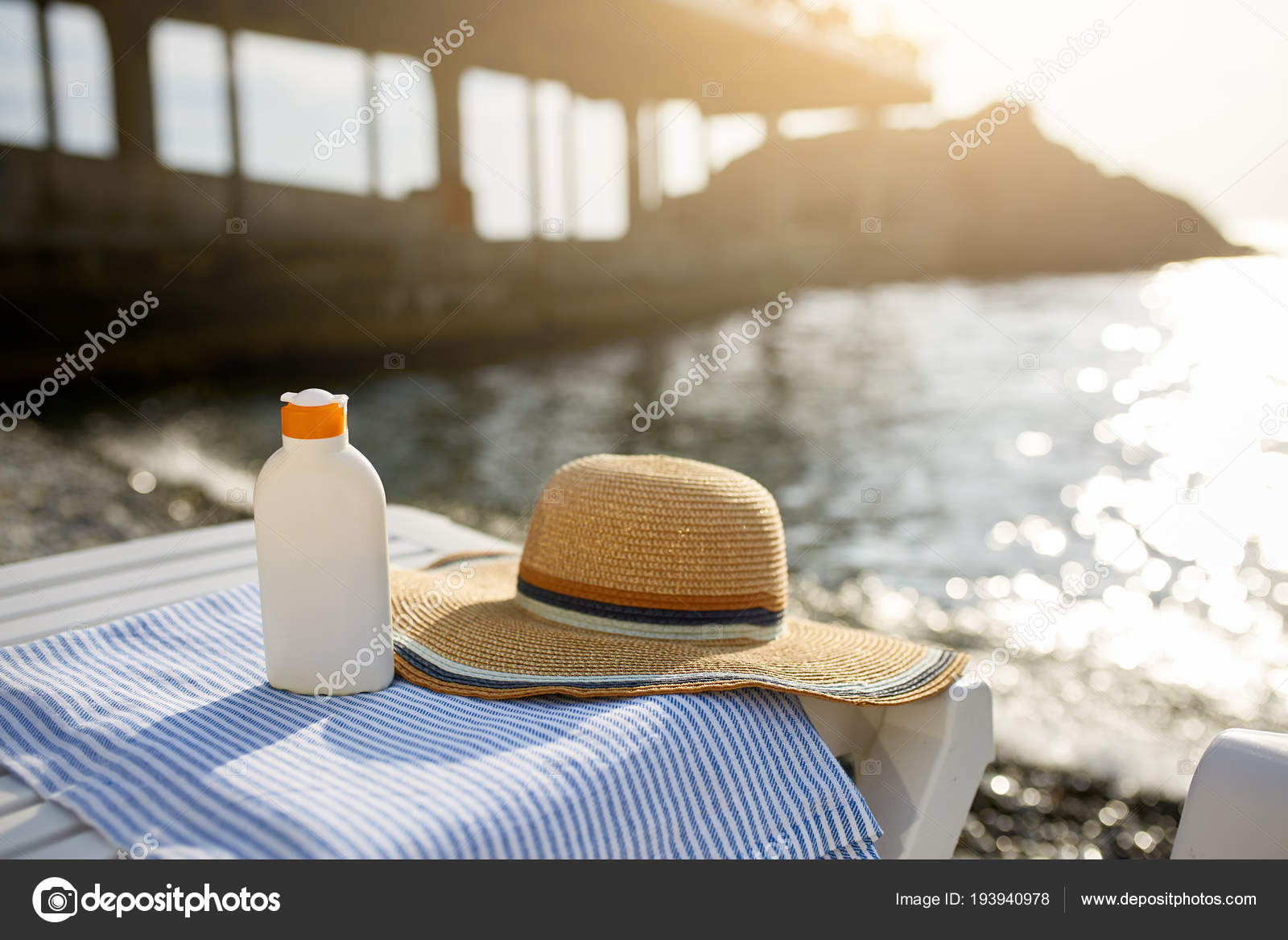 Suntan Cream Bottle On Beach Towel With Sea Shore On Background. Sunscreen  On Deck Chair Outdoors On Sunrise Or Sunset At Luxury Spa Resort.