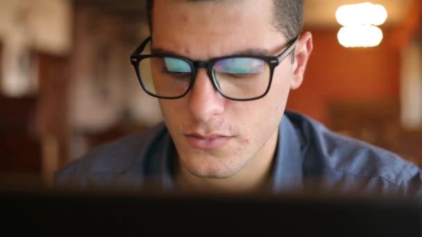 Detail odrazů obrazovky monitoru notebooku v mans brýle. Mladý bělošský Nezávislý podnikatel práci a prohlížení internetu v úřadu. Hacker v práci kradení databáze účtů