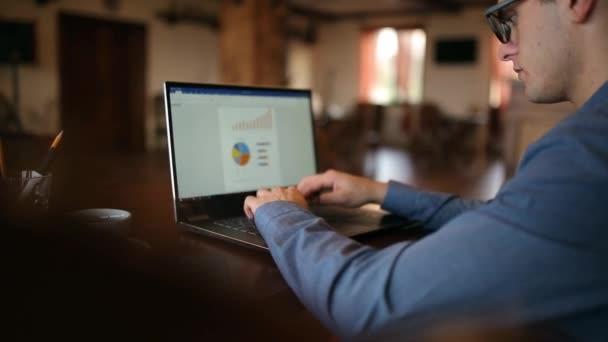 Vissza view freleancer üzletember szemüveg szorgalmasan dolgozik a laptop a kávézóban. Az ember gépelés-on billentyűzet számítógép-diagramok és trendek dokumentumot a képernyőn. Üzleti koncepció