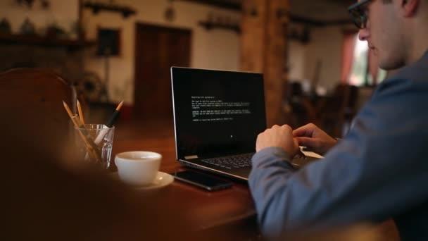 Uomo si accende un computer portatile attende caricamento computer e scopre è stato infettato da un virus spyware ransomware che chiede soldi recuperare i dati crittografati. Crossbones spaventoso teschio rosso sullo schermo