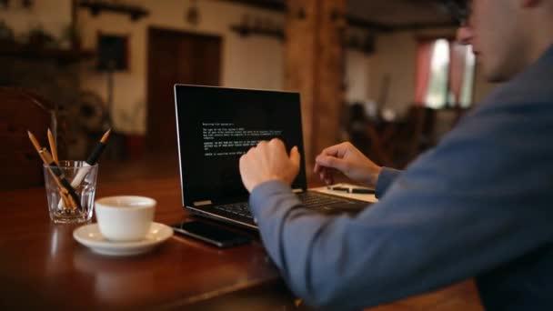 Uomo si accende un computer portatile attende caricamento computer e scopre è stato infettato da un virus spyware ransomware che chiede soldi recuperare i file di dati. Spaventoso teschio rosso sullo schermo