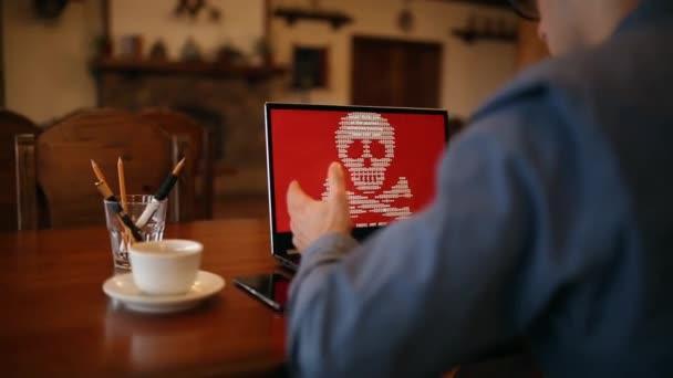 Uomo con un computer portatile venga infettato da un virus spyware ransomware che chiede soldi recuperare i file crittografati. Spaventosi rossi scintillante teschio e ossa incrociate sullo schermo