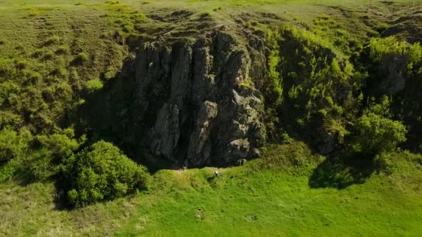 Aerial footage of camera flying over the picturesque valley, green fields and hills, rocky cliffs and mountains, rock log and river. Spring and summer season weekend at nature concept.