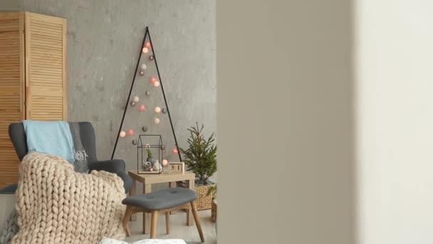 Stylové vánoční skandinávský interiér s elegantní křeslo a teplé merinos pléd. Pohodlí s nordic novoroční výzdobu domů. Minimalistický vánoční strom s girlandami a světla v místnosti se světlem.