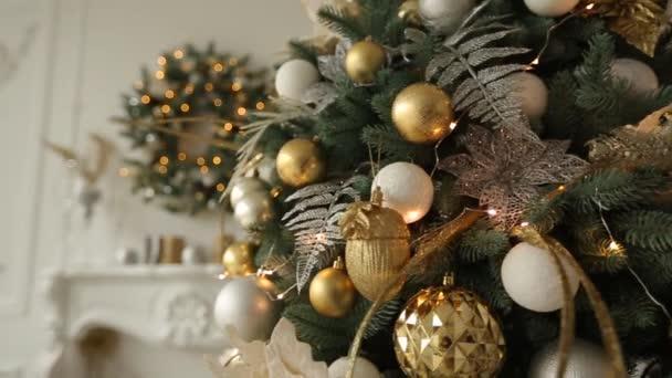 Stylový bílý interiér s jedle vánoční stromky a věnce plné zlaté ozdoby, hračky, světel a girlandy. Věnec na pozadí. New Years Eve doma.