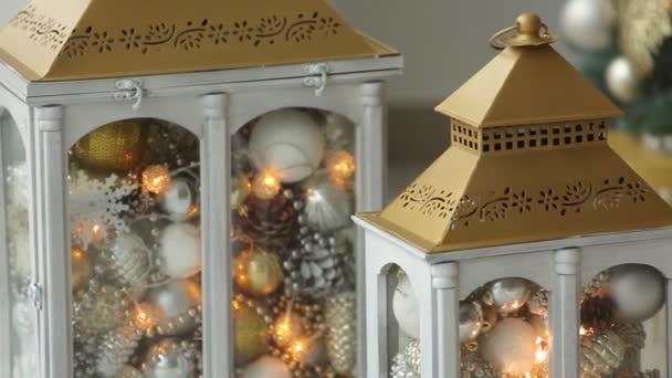 Interni eleganti di natale bianco con lanterne decorate, camino, lanterne, lampade, candele, dossi. Comfort di casa con lalbero di Natale pieno di ghirlande, luci e decorazioni dorate. New Years Eve.