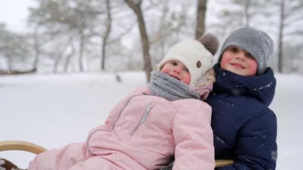 glückliche Familie Rodeln an einem verschneiten Wintertag. Vater und Mutter ziehen bei Schneefall Schlitten mit Sohn und Tochter. Jungen und Mädchen rodeln im Freien. Die Leute fahren Schlitten und genießen den Weihnachtsurlaub. Zeitlupe.