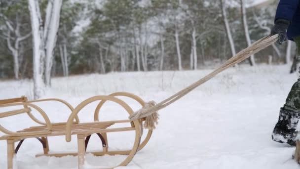 Roztomilý chlapec v teplém oblečení tahání dřevěné sáně na zasněžené zimní den. Malý kluk sáňkaří v parku na sněhu. Sledování záběru dítěte v námořní bundě, jak leze z kopce do saní v lese. Zpomalený pohyb.