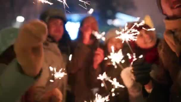 Friends have fun partying with sparklers and doing selfie photo on smartphone at Christmas market. People jump and dance at New Year fairground on winter night. Snowfall, bulb garlands on backdrop.