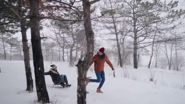 schönes Paar Rodeln an einem verschneiten Wintertag. Mann zieht Schlitten mit Freundin bei Schneefall Frau haben Spaß und rodeln draußen mit Freund. Die Leute fahren Schlitten und genießen den Weihnachtsurlaub. Zeitlupe.