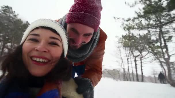 Selfie-Video eines schönen Paares beim Rodeln an einem Wintertag. Mann schiebt Schlitten mit Freundin bei Schneefall Frau haben Spaß und rodeln im Freien mit Freund hält Kamera. Menschen Schlittenfahrt und Dreharbeiten vlog.