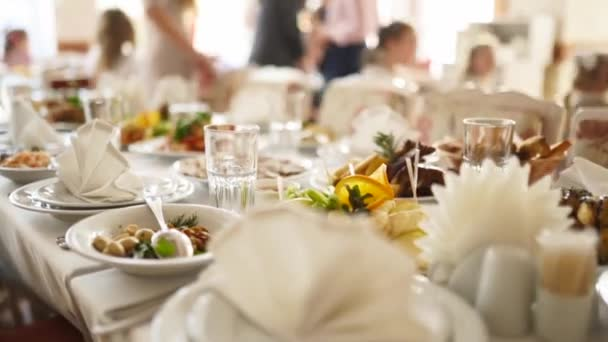 Beautifully served banquet table with different food snacks and appetizers in the sun on corporate christmas birthday party event or wedding celebration. Decorated catering in white interior.