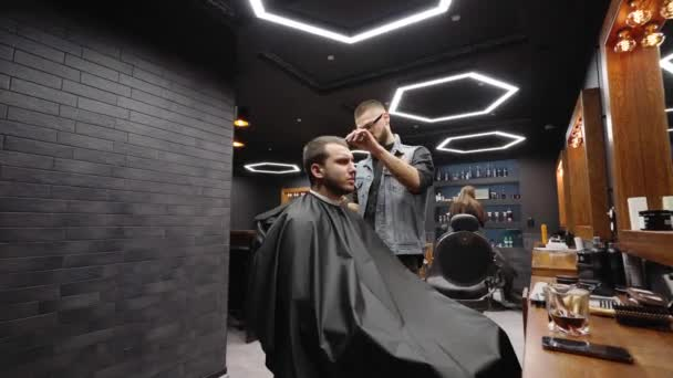 Trendy barber cuts bearded mans hair with a clipper in barbershop. Mens hairstyling and hair cutting in salon. Grooming the hair with trimmer. Hairdresser doing haircut in retro hair salon. Dolly in
