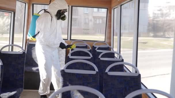 Pracovník týmu Hazmat dezinfikuje interiér autobusu antibakteriálními dezinfekčními tampony na koronavirovou covid-19 karanténu. Muž v plynové masce, ochranný oděv čistí místa ve veřejné dopravě, držadla s hadrem.