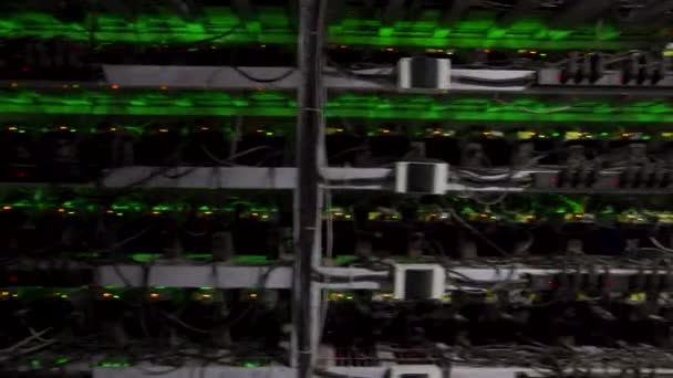 Velké úložiště datových center pro drátový internet. Zařízení pro těžbu kryptoměn na velké farmě. Horníci ASIC na stojanech dolují bitcoin v serverovně. Superpočítač bliká světly. Záběry Steadycam.