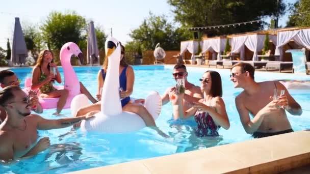 Freunde feiern mit Cocktails im Pool der Ferienvilla. Fröhliche junge Leute in Badebekleidung tanzen, Clubbing mit aufblasbarem Flamingo, Schwan, Matratze im Luxus-Resort an sonnigen Tagen. Zeitlupe