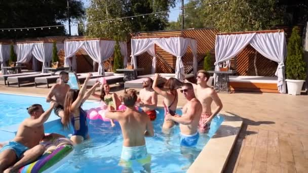 Multiracial group of friends having party in a private villa swimming pool. Happy young people in swimwear dancing and clubbing with inflatable flamingo, swan, mattress in luxury resort. Slowmo.