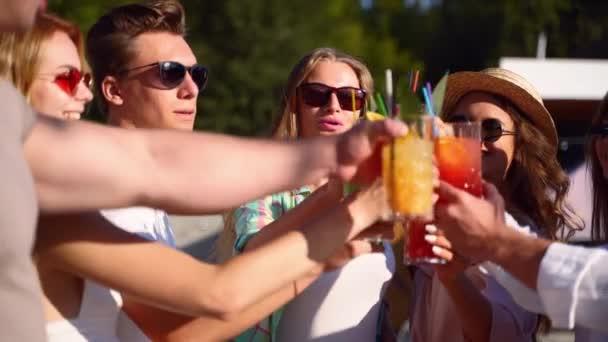 Nahaufnahme von Freunden, die sich beim Sommerfest am Pool amüsieren, Gläser mit frischen Sommercocktails in der Nähe des Hotelschwimmbeckens im Freien klirren. Menschen stoßen in Zeitlupe auf Saft in Luxusvilla an.