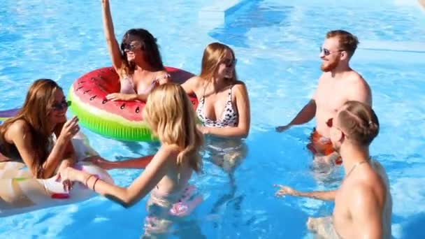 Friends have party in a private villa swimming pool. Happy young people in swimwear dancing, bonding and clubbing with floaties and inflatable mattress in luxury resort on sunny day. Slow motion.