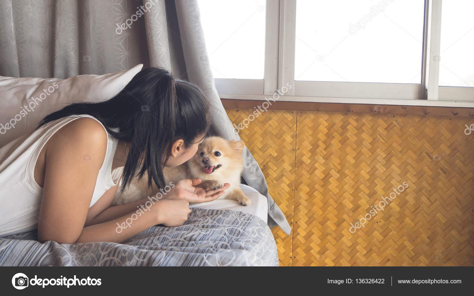 Frau mit Hund im Schlafzimmer entspannen — Stockfoto © sevendeman ...