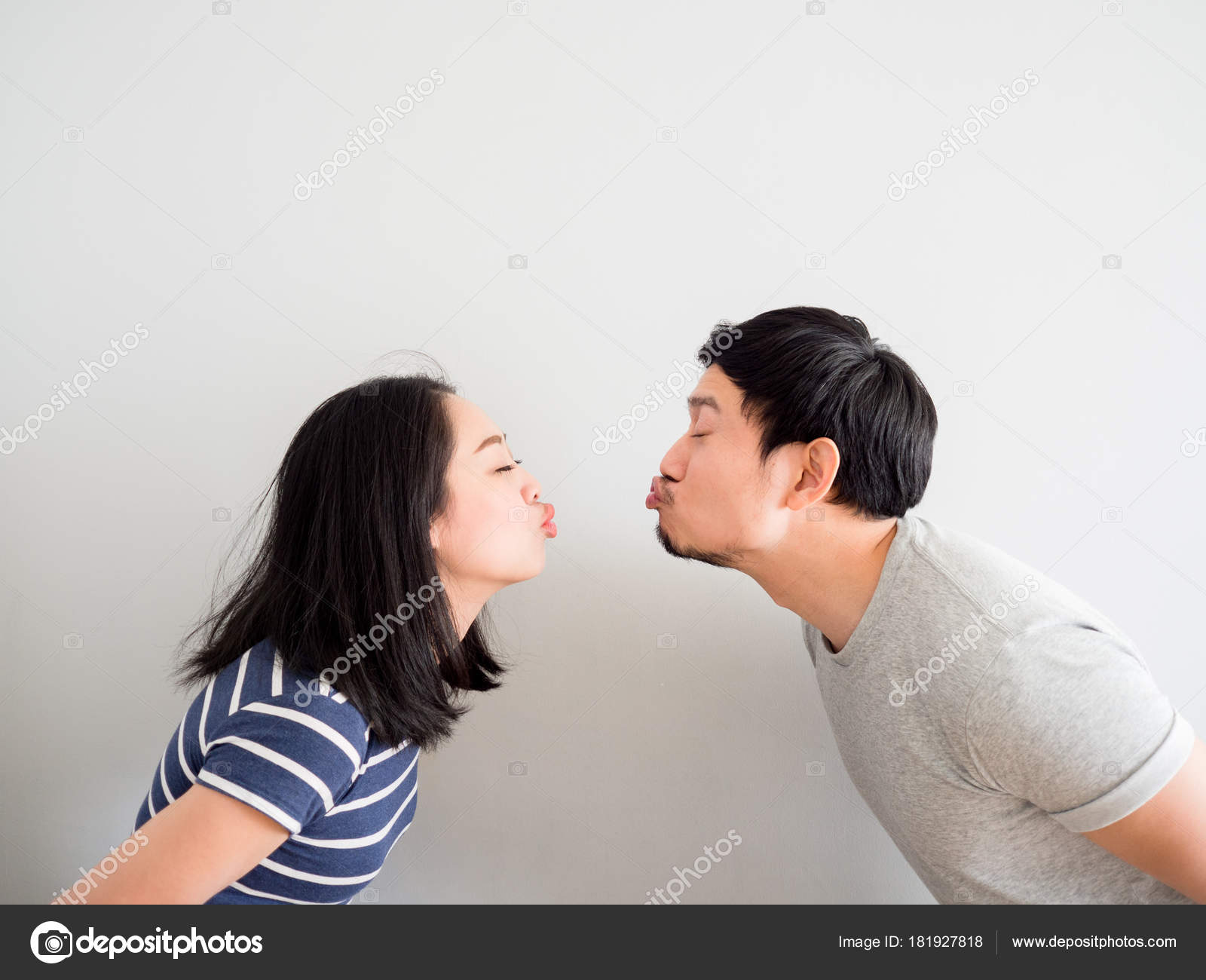 funny lovely couple trying to kiss each other concept of comedy