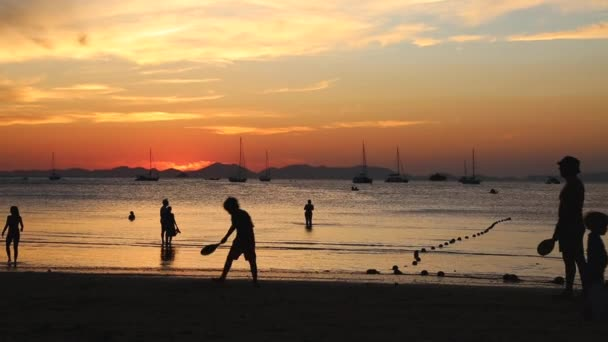 Silhouettes on a sunset background on a tropical beach. Family, father and son play badminton, daughter takes selfie.