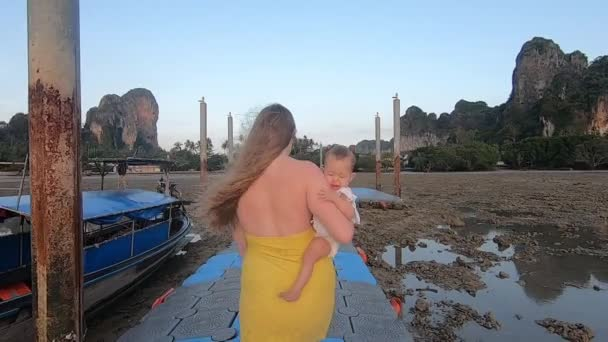 A woman in a yellow dress carries in her arms a child on a pontoon pier during a high tide. Mom walks with her daughter at dawn at sea. Family holiday.