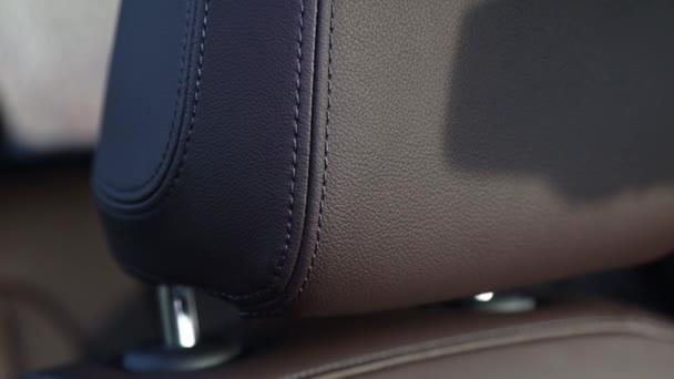 Detaily zblízka koženého interiéru vozu se stehem.