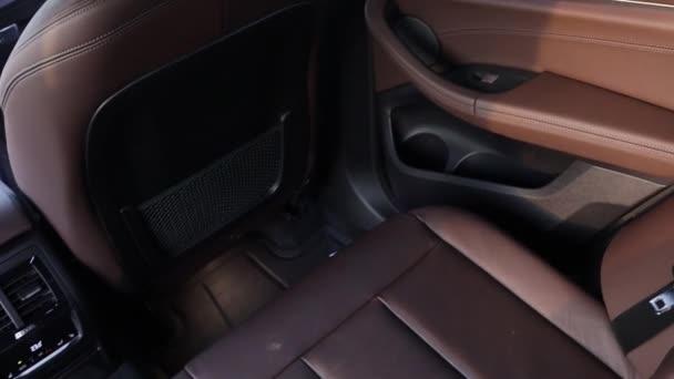 Interiér z hnědé kůže v prvotřídním SUV. Zadní sedadla, pohled shora na klimatizaci, dveře a sedadla