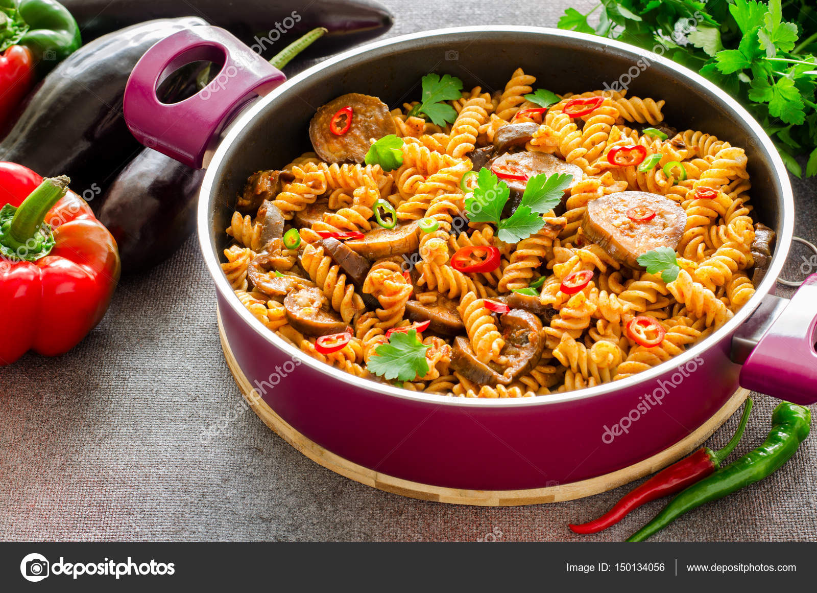 Superior Mediterranean Eggplant Pasta In Pot With Tomatoes, Red Pepper And Parsley  On Grey Background.