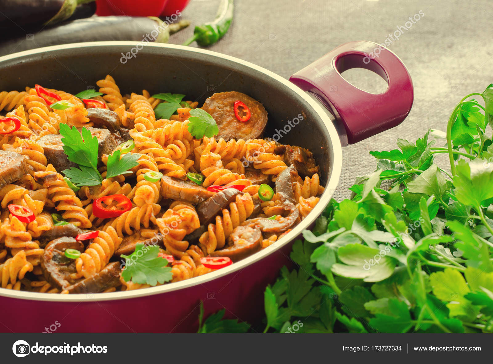 Exceptional Mediterranean Eggplant Pasta In Pot With Tomatoes, Red Pepper And Parsley  On Grey Background.