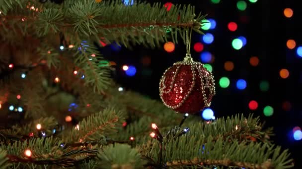 magically decorated christmas tree with balls ribbons and red garlands on a blurred green shiny