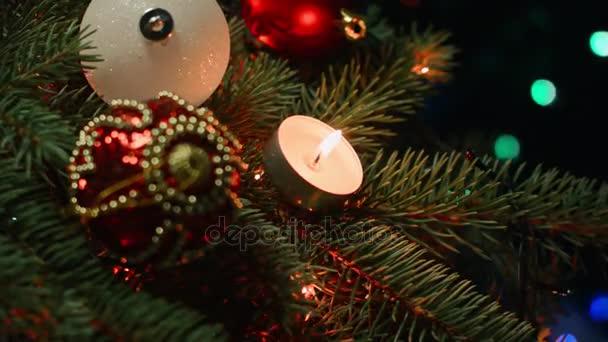 Weihnachtsschmuck am Weihnachtsbaum mit Kerzen auf einem Hintergrund Girlanden