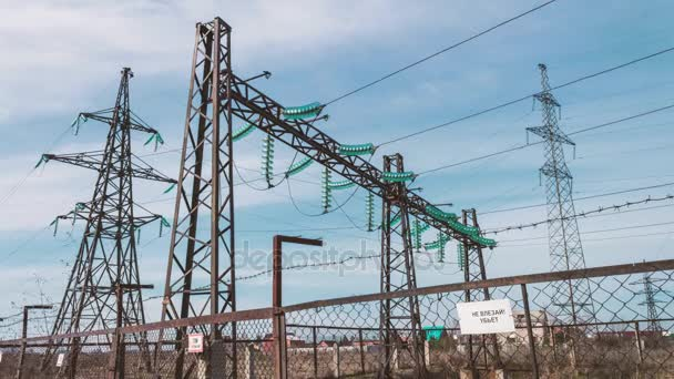 High-voltage electrical substation. Pylons with insulators and wires behind a protective fence. Electric and power industry. Production of electricity and transporting it to cities. Generators and