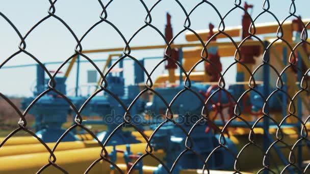 Öl- und Gasanlage. Pumpwerk hinter dem Zaun im Defokus. Maschendraht. Rückschlagventile an der Pipeline. Ölindustrie. Förderung von Erdgas. Reinigungs- und Lagerungsstation.