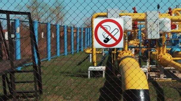 Erdgas. Reinigungs- und Transportstation. Verarbeitung von Gas und Öl. Pipeline mit Manometer und Pumpe. Ölindustrie. Rauchen verboten. Warnung am Zaun. Brandgefahr. Gelbe Pipeline