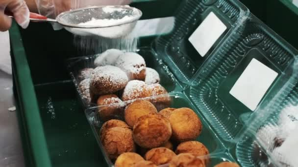 Fried donut sprinkled with white sugar powder. Sweet tooth. Delicious pastries. Production of donuts and packaging.