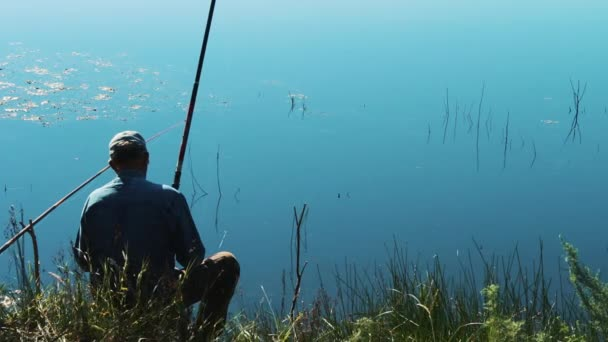 Rybář loví s rybářským prutem na řece. Rybář na letní rybaření. Rybář chytí rybářský prut z pobřeží