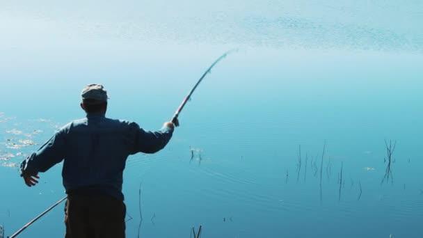 Rybář je házení rybářský prut do jezera lovit ryby. Sportovní rybaření. Zbytek na vzduchu. Krásné ráno příroda.