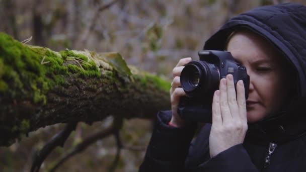 dívka fotograf procházky podzimním lesem a fotí přírody. filmový záběr. Zpomalený pohyb