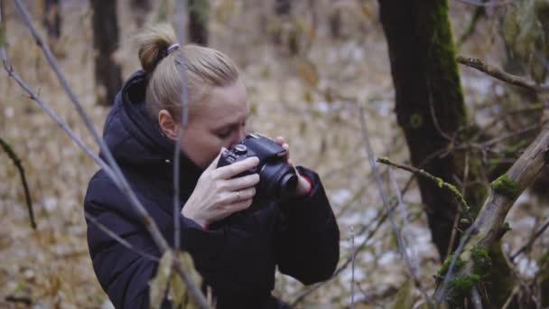 a fotós a lány séta egy őszi fa és a természet képei. az első hó. filmszerű lövés. lassú mozgás utazó